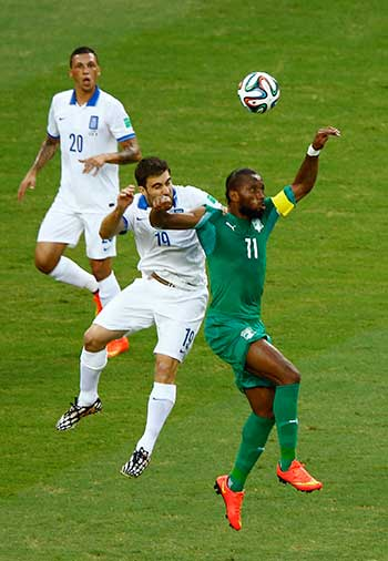 Greece's Papastathopoulos and Ivory Coast's Drogba jump for ball during their 2014 World Cup Group C soccer match at the Castelao arena in Fortaleza
